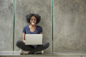 Young woman sitting on corridor floor with digital tablet